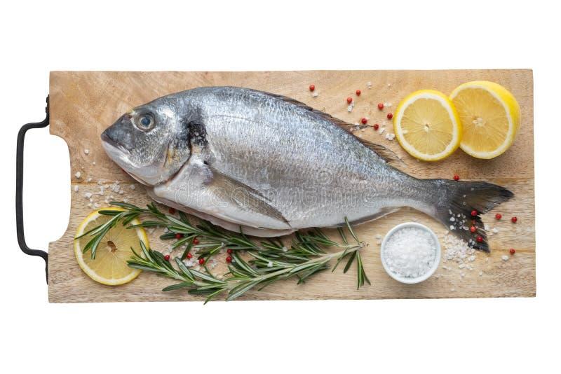 Φρέσκα ψάρια dorado με τις φέτες, το άλας και το δεντρολίβανο λεμονιών στον τέμνοντα πίνακα τοπ άποψη, στοκ φωτογραφία