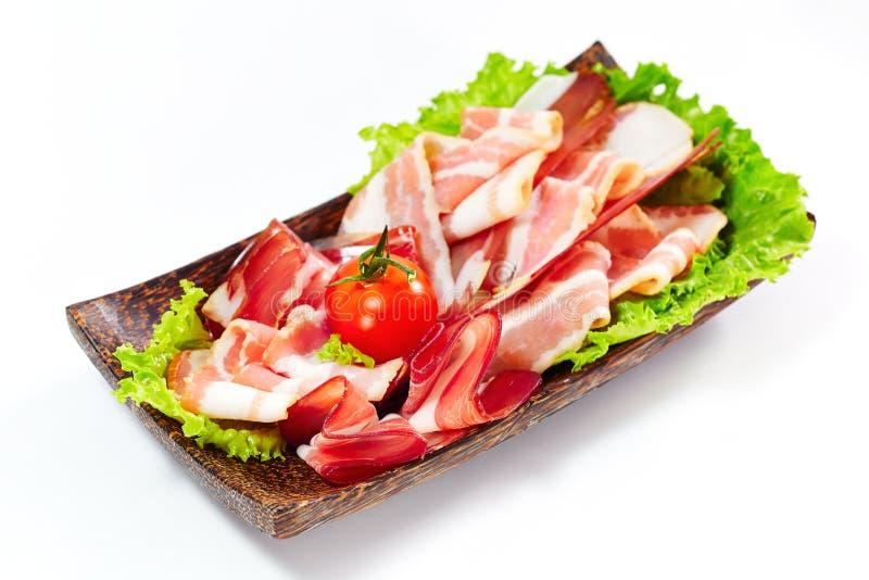 Φρέσκα λωρίδες μπέϊκον που εξυπηρετούνται με τα πράσινα και την ντομάτα. Στο λευκό. στοκ εικόνα με δικαίωμα ελεύθερης χρήσης