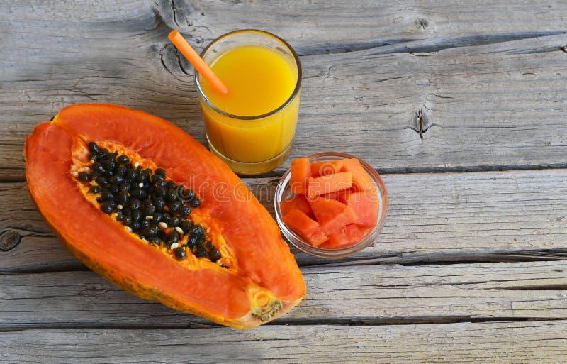 Φρέσκα ώριμα οργανικά papaya τροπικά φρούτα που κόβονται στο μισό, που τεμαχίζονται και papaya το χυμό σε ένα βάζο γυαλιού στο πα στοκ εικόνα με δικαίωμα ελεύθερης χρήσης