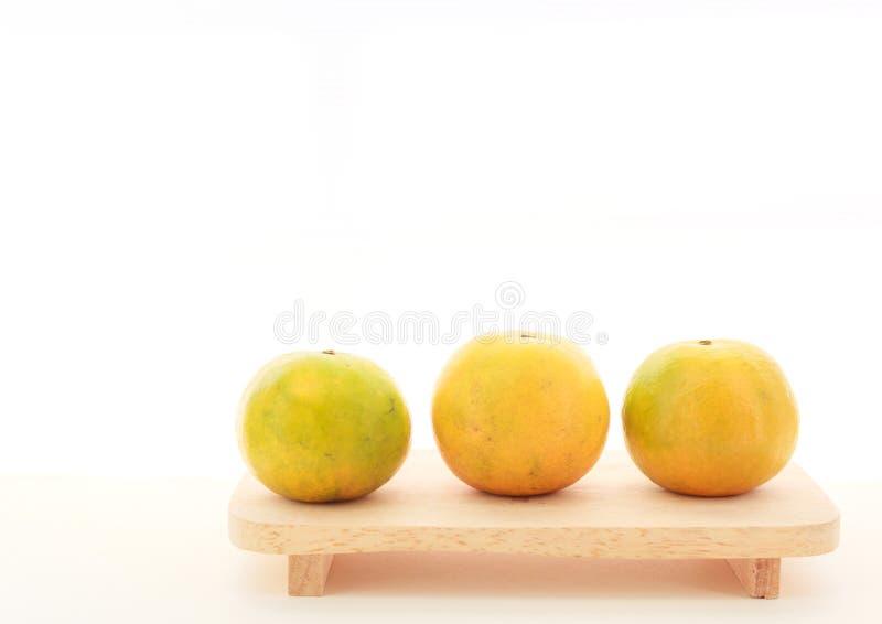 Φρέσκα ώριμα πράσινα και πορτοκαλιά tangerine εσπεριδοειδή, μανταρίνια, φρούτα στον ξύλινο δίσκο στο άσπρο επιτραπέζιο υπόβαθρο ε στοκ φωτογραφία