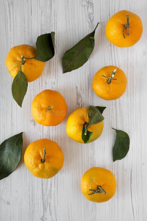 Φρέσκα ώριμα unshelled tangerines σε ένα άσπρο ξύλινο υπόβαθρο, τοπ άποψη Επίπεδος βάλτε, άνωθεν, τα γενικά έξοδα στοκ φωτογραφία