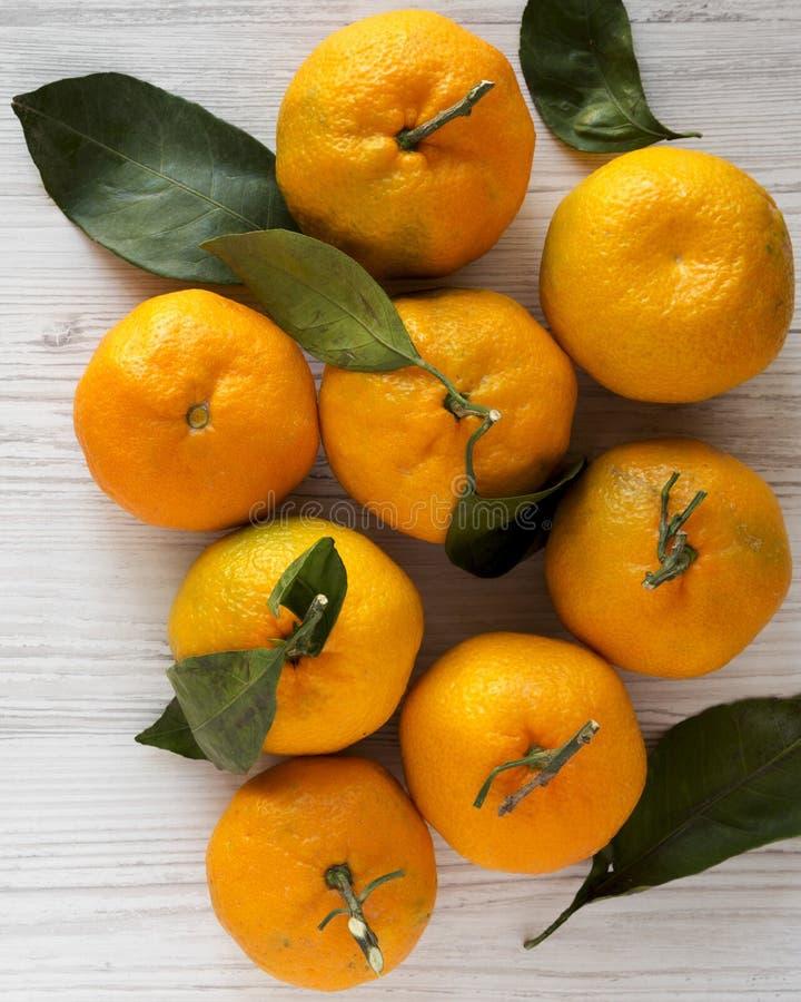 Φρέσκα ώριμα unshelled tangerines σε ένα άσπρο ξύλινο υπόβαθρο, υπερυψωμένη άποψη Επίπεδος βάλτε, άνωθεν στοκ φωτογραφία με δικαίωμα ελεύθερης χρήσης