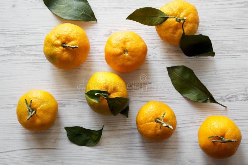 Φρέσκα ώριμα unshelled tangerines σε μια άσπρη ξύλινη επιφάνεια, τοπ άποψη Επίπεδος βάλτε, άνωθεν στοκ εικόνες