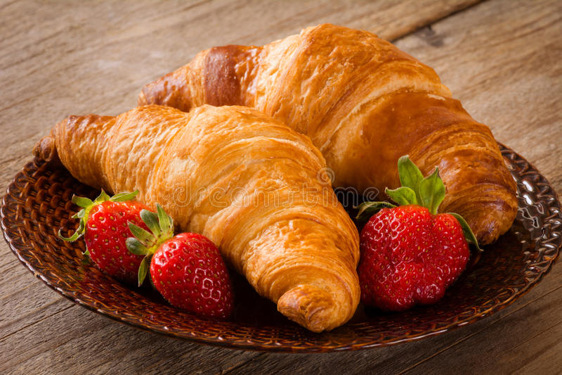 Φρέσκα croissants με τις φράουλες στο πιάτο, τρόφιμα προγευμάτων, θερμός τόνος στοκ φωτογραφίες