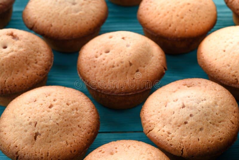 Φρέσκα muffins σε έναν τέμνοντα πίνακα σε ένα ξύλινο μπλε υπόβαθρο BA στοκ φωτογραφία
