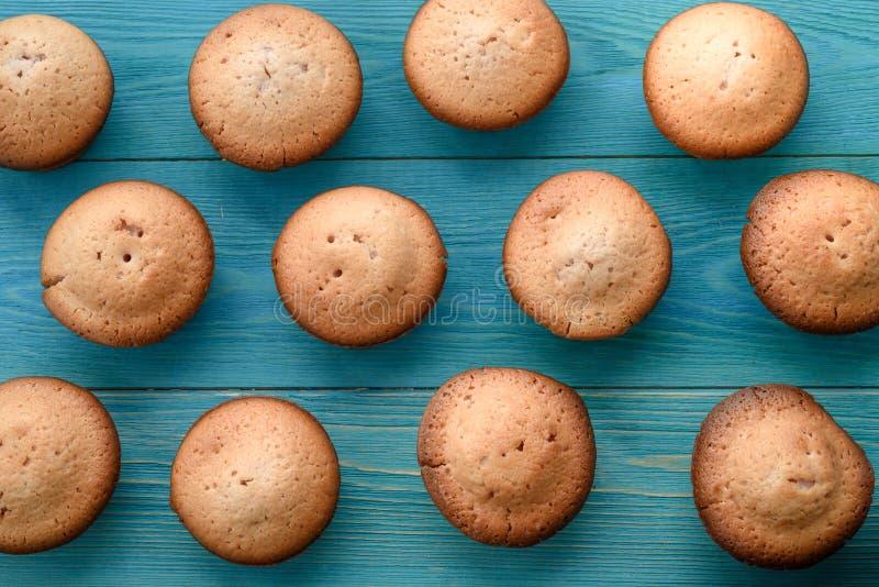 Φρέσκα muffins σε έναν τέμνοντα πίνακα σε ένα ξύλινο μπλε υπόβαθρο BA στοκ εικόνα