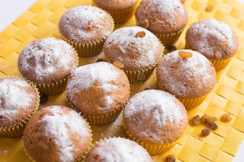 Φρέσκα muffins στην κίτρινη πετσέτα στοκ εικόνα