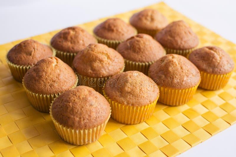 Φρέσκα muffins στην κίτρινη πετσέτα στοκ εικόνες