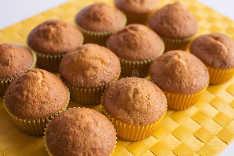 Φρέσκα muffins στην κίτρινη πετσέτα στοκ φωτογραφίες
