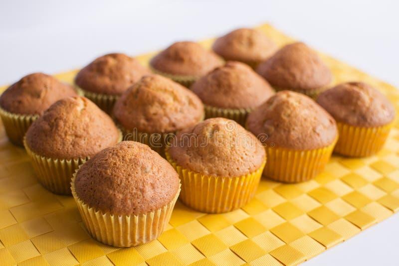 Φρέσκα muffins στην κίτρινη πετσέτα στοκ φωτογραφία με δικαίωμα ελεύθερης χρήσης