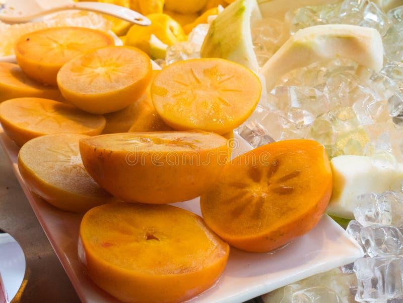 Φρέσκα Persimmon περικοπών φρούτα που αναμιγνύονται με τον κύβο πάγου στοκ εικόνα