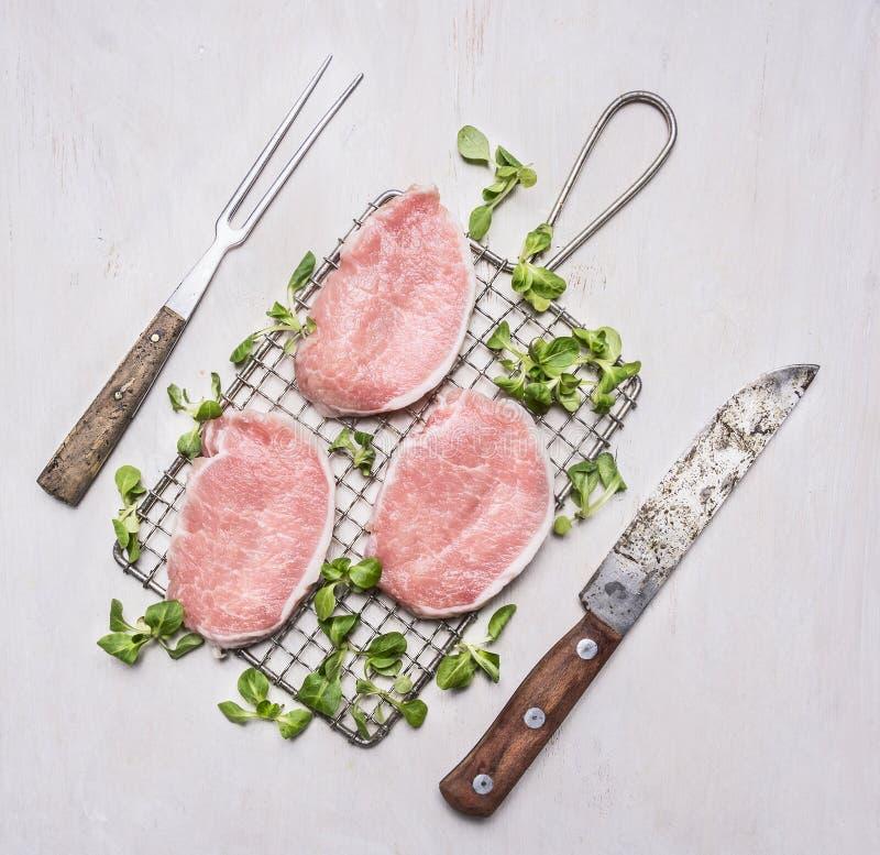 Φρέσκες ακατέργαστες μπριζόλες χοιρινού κρέατος με τα χορτάρια, ένα μαχαίρι και ένα δίκρανο για το κρέας στη σχάρα για τοπ άποψη  στοκ εικόνες με δικαίωμα ελεύθερης χρήσης