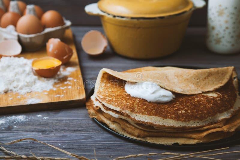 Φρέσκες, καυτές τηγανίτες σε ένα τηγανίζοντας τηγάνι, αυγά, γάλα, αλεύρι σε έναν ξύλινο πίνακα στοκ εικόνα με δικαίωμα ελεύθερης χρήσης