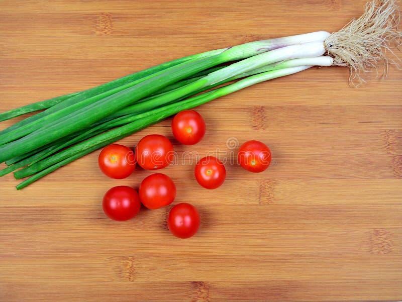 Φρέσκες κόκκινες ντομάτες κερασιών και πράσινο κρεμμύδι ανοίξεων στο ξύλινο υπόβαθρο στοκ εικόνες με δικαίωμα ελεύθερης χρήσης