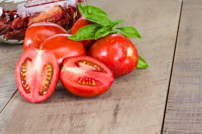 Φρέσκες κόκκινες ντομάτες κολλών με το βάζο στοκ εικόνες