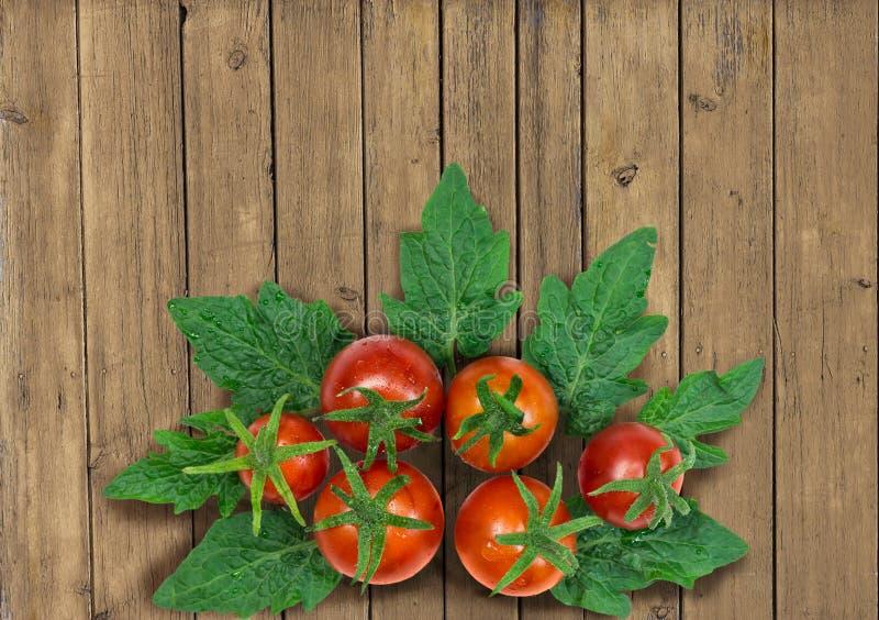 Φρέσκες κόκκινες ντομάτες στο καλάθι στο ξύλινο υπόβαθρο στοκ φωτογραφίες
