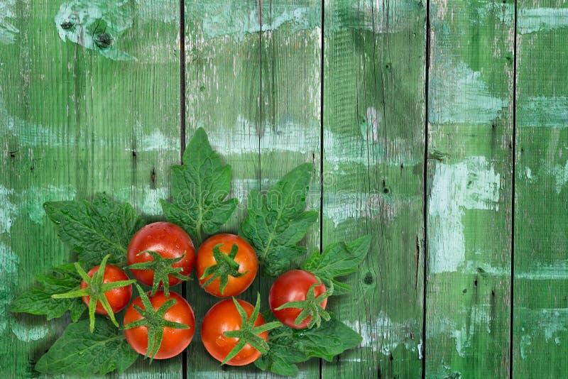 Φρέσκες κόκκινες ντομάτες στο καλάθι στο ξύλινο υπόβαθρο στοκ εικόνα