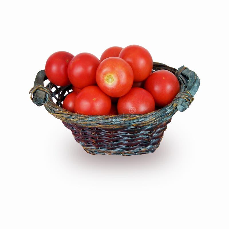 Φρέσκες κόκκινες ντομάτες στο ψάθινο καλάθι στο άσπρο υπόβαθρο στοκ εικόνα