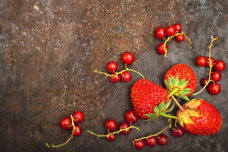 Φρέσκες κόκκινη σταφίδα και φράουλα με τη μέντα Σε ένα παλαιό μαύρο υπόβαθρο Τοπ όψη Κινηματογράφηση σε πρώτο πλάνο στοκ εικόνες