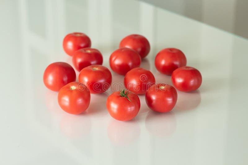 Φρέσκες ντομάτες σε έναν άσπρο πίνακα γυαλιού Συγκομίζοντας ντομάτες r στοκ φωτογραφία