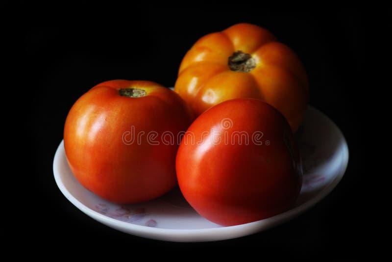 Φρέσκες ντομάτες σε ένα πιάτο σε ένα σκοτεινό υπόβαθρο στοκ φωτογραφίες