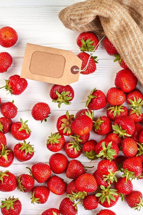 Φρέσκες φράουλες και καφετιά ετικέτα χαρτονιού στοκ φωτογραφία