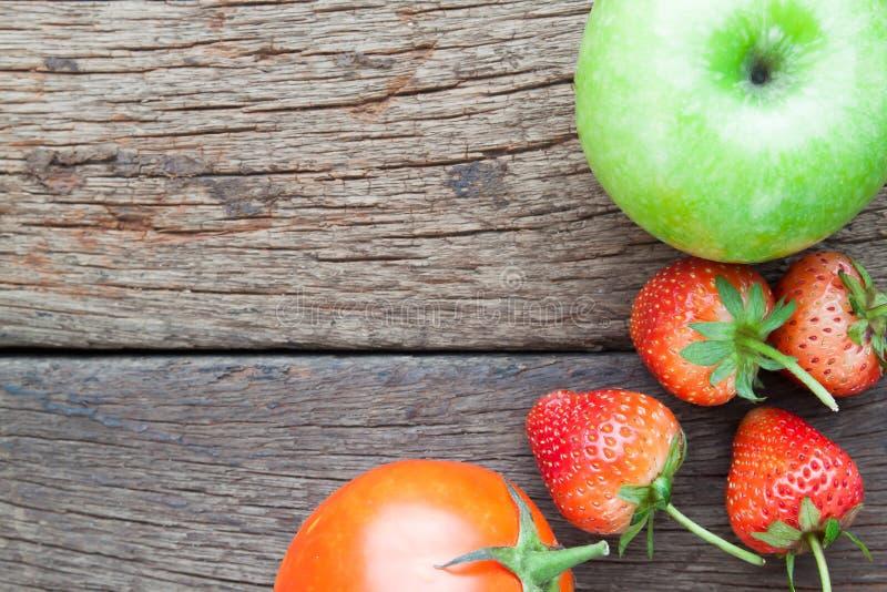 Φρέσκες φράουλες, πράσινες μήλο και ντομάτα στο ξύλινο υπόβαθρο, στοκ εικόνες