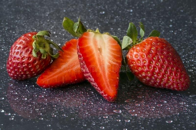 Φρέσκες φράουλες σε ένα μαύρο υπόβαθρο με τις πτώσεις του νερού στοκ εικόνα με δικαίωμα ελεύθερης χρήσης