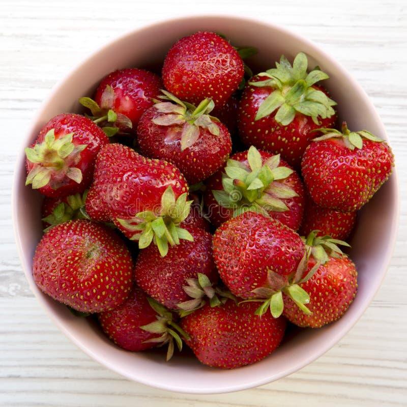Φρέσκες φράουλες σε ένα ρόδινο κύπελλο στο άσπρο ξύλινο υπόβαθρο, υπερυψωμένη άποψη στοκ φωτογραφία