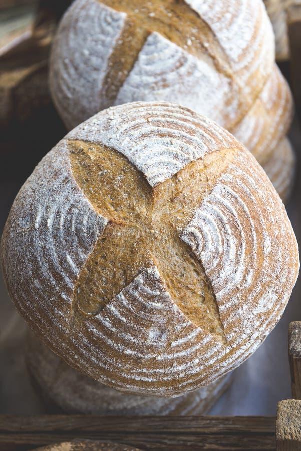 Φρέσκες φραντζόλες του στρογγυλού ψωμιού στον ξύλινο δίσκο στοκ εικόνες με δικαίωμα ελεύθερης χρήσης