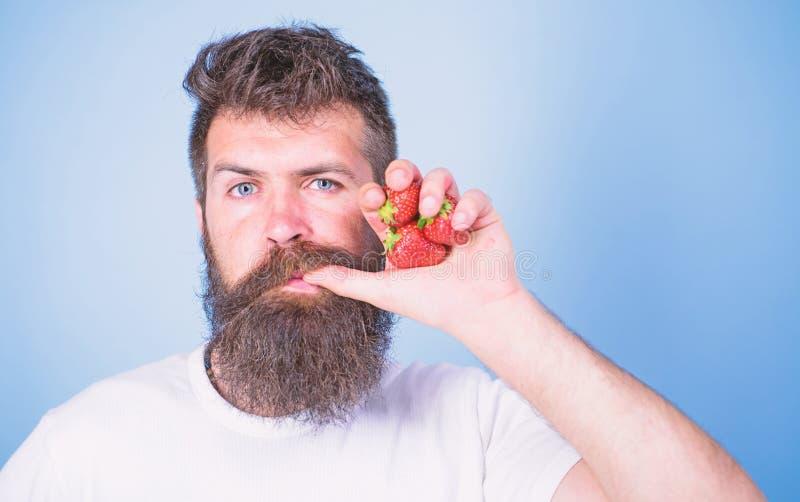 φρέσκια έννοια χυμού Το άτομο πίνει το χυμό φραουλών απορροφά τον αντίχειρα ως μπλε υπόβαθρο αχύρου ποτών Το Hipster γενειοφόρο κ στοκ φωτογραφία με δικαίωμα ελεύθερης χρήσης