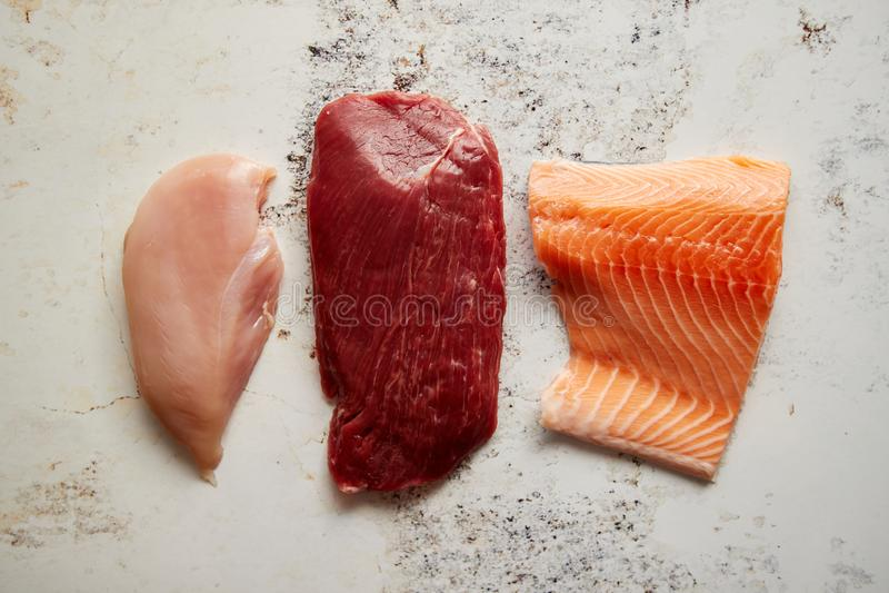Φρέσκια ακατέργαστη μπριζόλα βόειου κρέατος, στήθος κοτόπουλου, και λωρίδα σολομών στοκ φωτογραφία