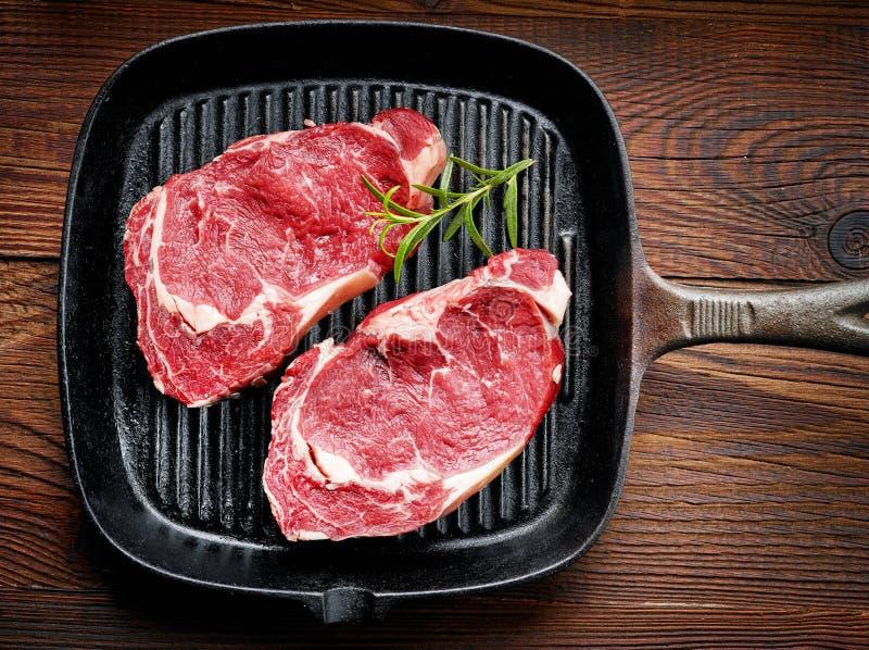 Φρέσκια ακατέργαστη μπριζόλα βόειου κρέατος στο μαγείρεμα του τηγανιού στοκ φωτογραφίες