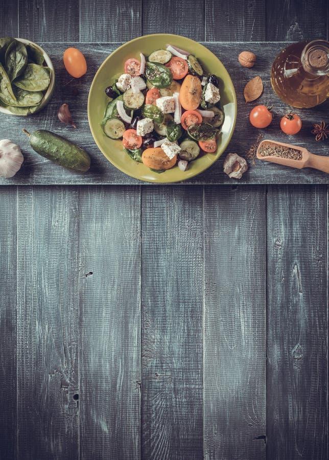 φρέσκια ελληνική σαλάτα στο πιάτο και τα συστατικά στοκ εικόνα με δικαίωμα ελεύθερης χρήσης