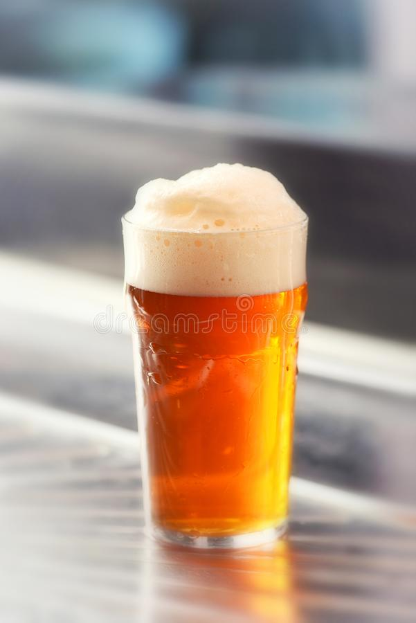 Φρέσκια εξυπηρετούμενη πίντα της frothy μπύρας σχεδίων σε ένα γυαλί στοκ εικόνα με δικαίωμα ελεύθερης χρήσης