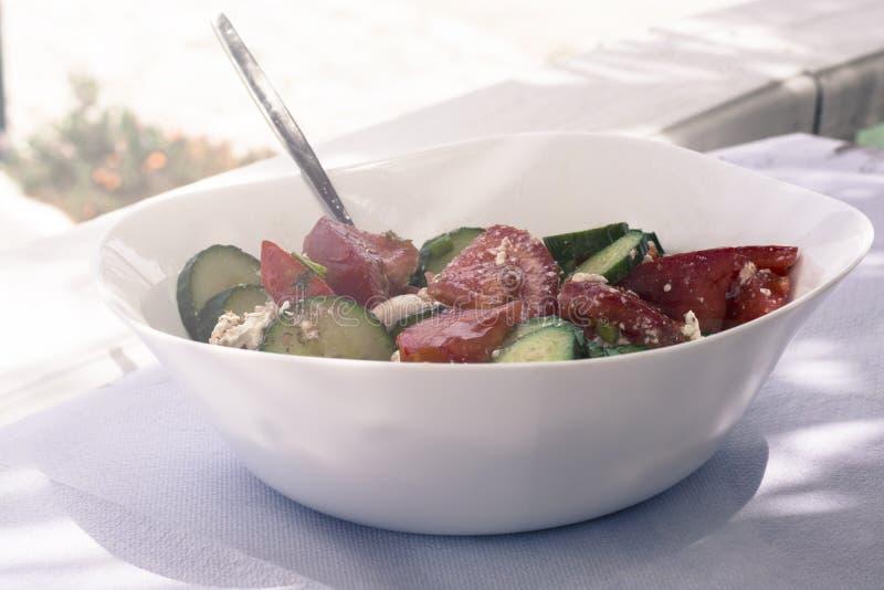 Φρέσκια ελληνική σαλάτα σε ένα άσπρο πιάτο στον ήλιο στο νησί της Κρήτης στοκ εικόνες
