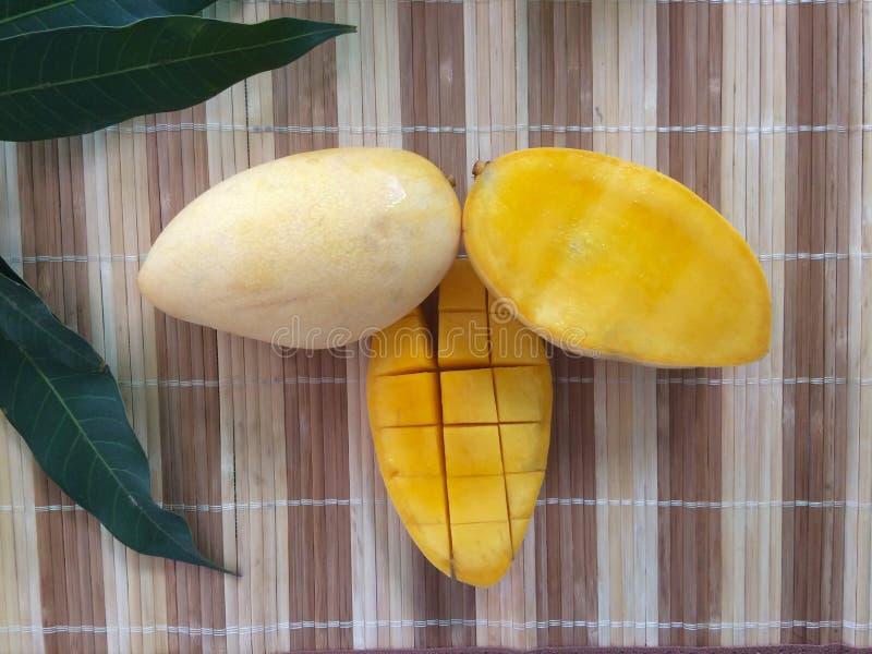 Φρέσκια κίτρινη φέτα μάγκο που κόβεται στους κύβους και το φύλλο στοκ εικόνες