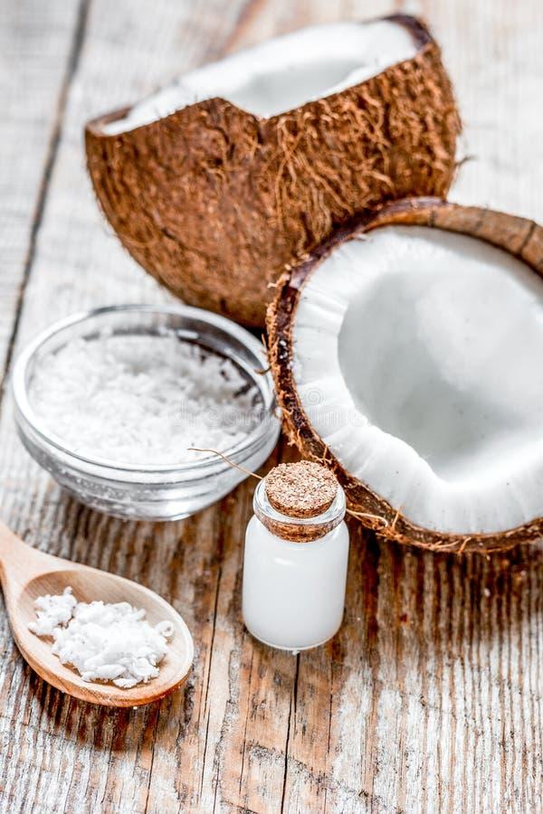 Φρέσκια καρύδα με το καλλυντικό πετρέλαιο στο βάζο στο ξύλινο υπόβαθρο στοκ φωτογραφία
