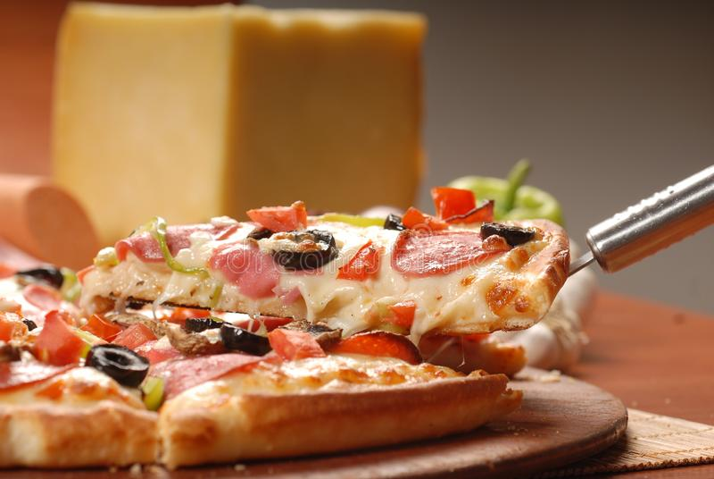 Καυτή φέτα πιτσών με το λειώνοντας τυρί σε έναν αγροτικό ξύλινο πίνακα στοκ φωτογραφία