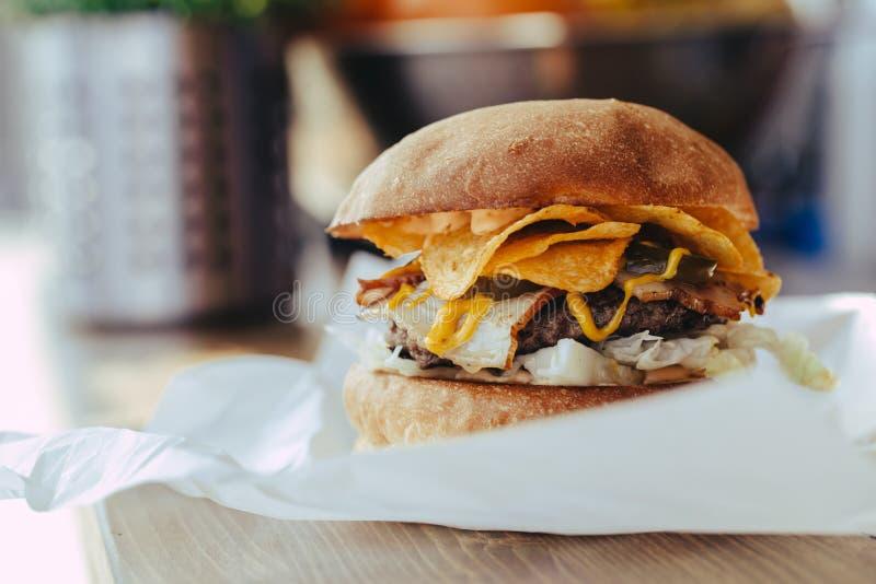 Φρέσκια κινηματογράφηση σε πρώτο πλάνο σπιτικό burger σχεδιαστών με cutlet, το μπέϊκον, τα τσιπ και τη σάλτσα μουστάρδας στο έγγρ στοκ φωτογραφίες