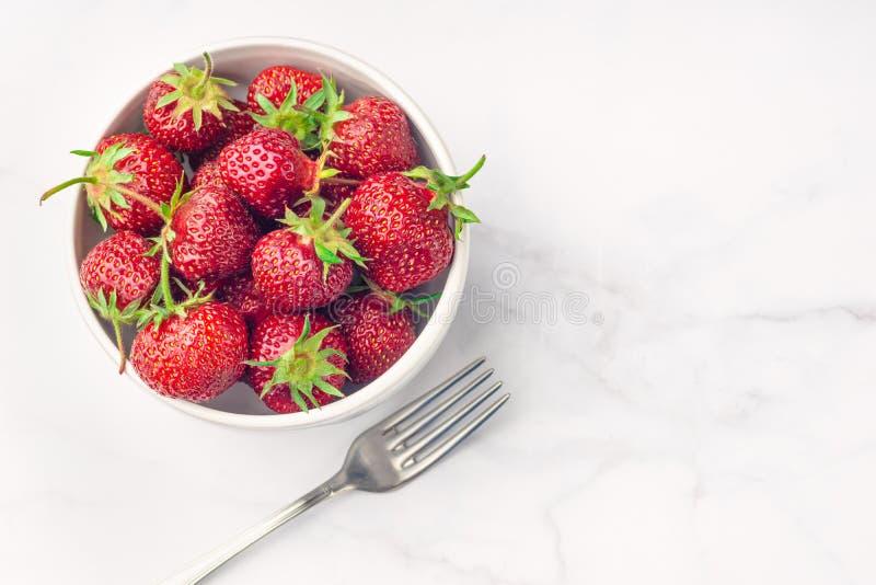 Φρέσκια οργανική φράουλα στο άσπρα κύπελλο και το δίκρανο, στο άσπρο υπόβαθρο στοκ φωτογραφίες με δικαίωμα ελεύθερης χρήσης