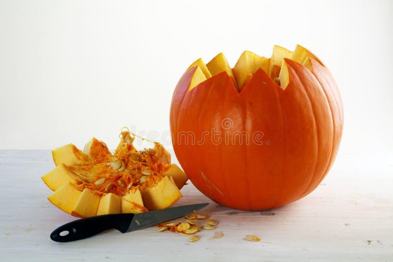 Φρέσκια πορτοκαλιά κολοκύθα που κόβεται ανοικτή με το καπάκι και το μαχαίρι στο άσπρο painte στοκ εικόνα