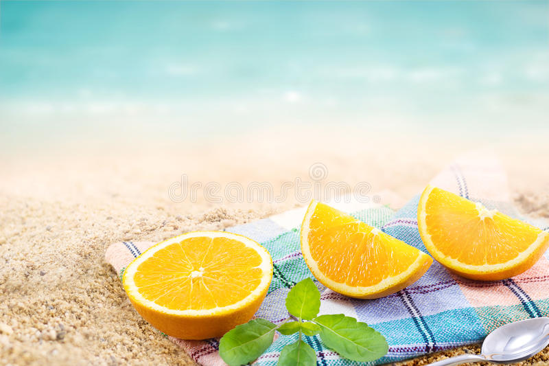 Φρέσκια πορτοκαλιά φέτα τμημάτων με τη μέντα τη θερινή ημέρα παραλιών θάλασσας υφάσματος και άμμου στοκ εικόνες
