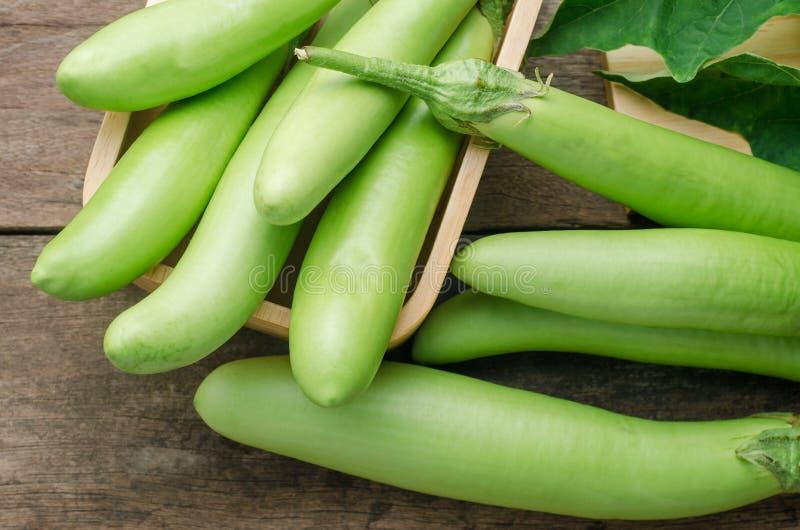 Φρέσκια πράσινη μελιτζάνα με τα φύλλα στο ξύλινο επιτραπέζιο υπόβαθρο στοκ εικόνες