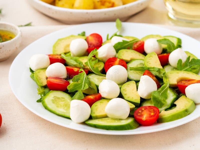 Φρέσκια σαλάτα με τη μοτσαρέλα και το avoca arugula αγγουριών ντοματών στοκ εικόνες
