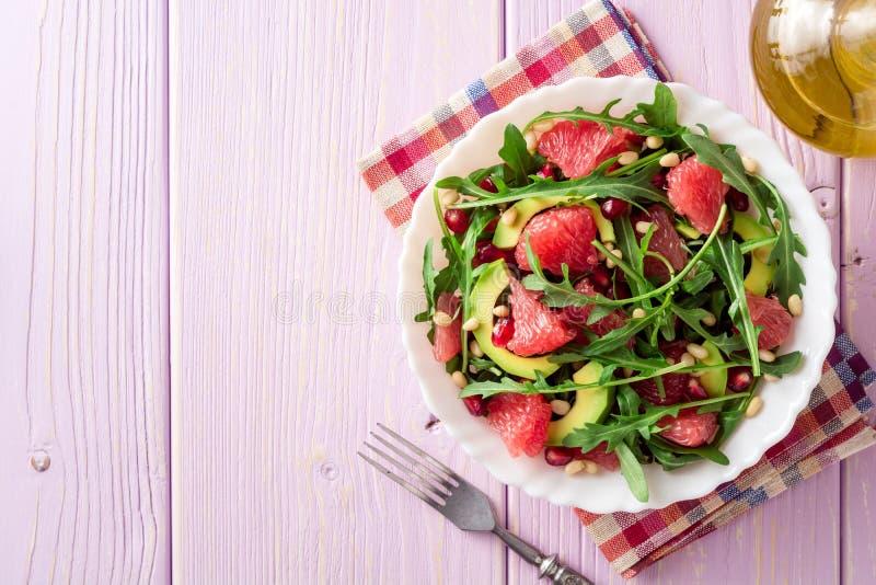 Φρέσκια σαλάτα με το arugula, το γκρέιπφρουτ, το αβοκάντο, τους σπόρους ροδιών και τα καρύδια πεύκων στοκ φωτογραφία με δικαίωμα ελεύθερης χρήσης