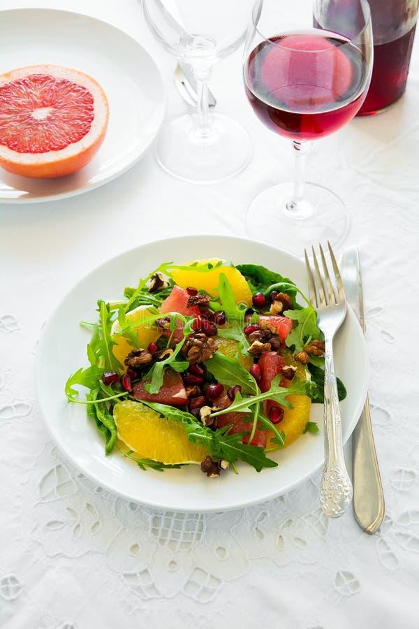 Φρέσκια σαλάτα με το arugula, το πορτοκάλι, το γκρέιπφρουτ, τα ξύλα καρυδιάς και τους σπόρους ροδιών στο άσπρο επιτραπέζιο ύφασμα στοκ φωτογραφίες με δικαίωμα ελεύθερης χρήσης