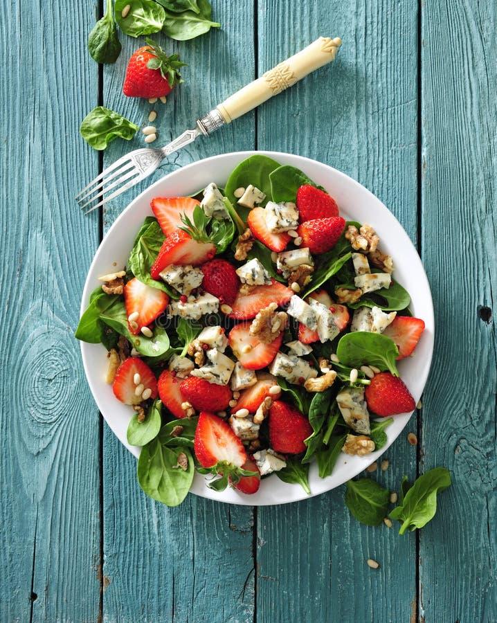 Φρέσκια σαλάτα φραουλών με τα φύλλα σπανακιού, το μπλε τυρί και τα ξύλα καρυδιάς στοκ εικόνες