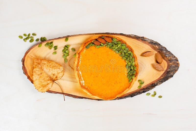 Φρέσκια σπιτική πίτα κολοκύθας που διακοσμείται με τους σπόρους και τα καρύδια στοκ φωτογραφίες