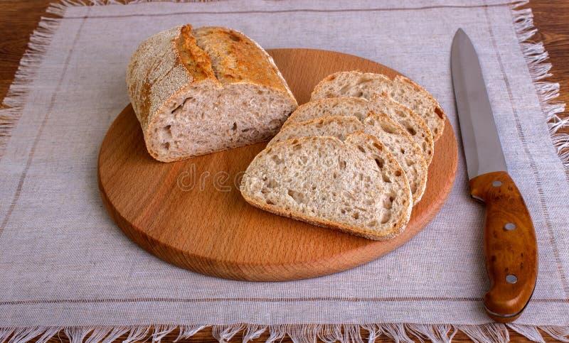 Φρέσκια φέτα ψωμιού και τέμνον μαχαίρι στον πίνακα στοκ εικόνες